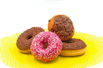 pinke Donuts, Schoko Donuts und Muffins auf einem gelben Deckchen.