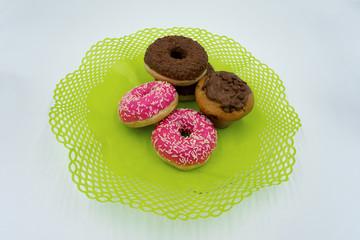 pinke Donuts, Schoko Donuts und Muffins auf einem grünen Deckchen.