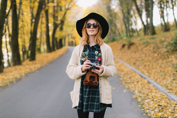 Hippie girl with old camera in a sunglasses, knitted sweater and hat walks autumn park.