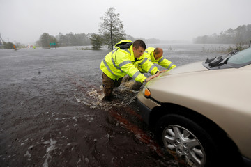 Police officers help push a stalled car that became stranded in rising flood waters while trying to cross an inundated bridge, after Hurricane Florence struck in Boiling Spring Lakes