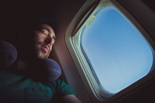 Young man with neck pillow resting and sleeping on an airplane
