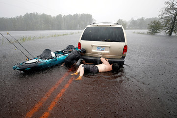 Jordan McKeon and Nathaniel Harrison try to free stalled car after Hurricane Florence struck in Boiling Spring Lakes