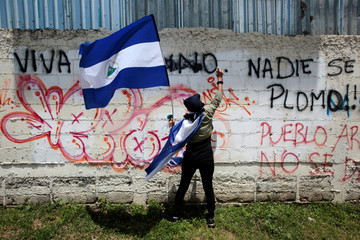 An anti-government protester sprays graffiti paint on a wall during a protest against Nicaraguan President Daniel Ortega's government in Managua