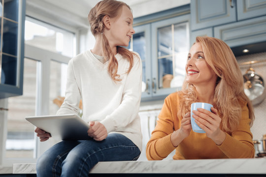 Lets discuss it. Cheerful blonde woman keeping smile on face and enjoying her talk with daughter