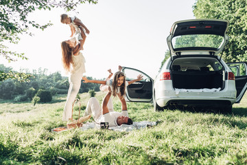 Adult couple with their little children having picnic in the Park Outside the City, Family Weekend Concept, Four People Enjoying Summer Time