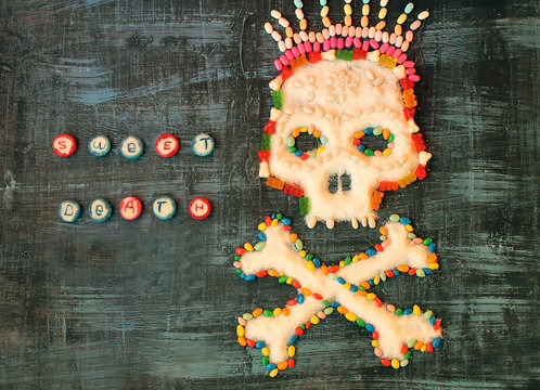 """concept  image of the skull and bones making of sugar and colored candies with the inscription """"sweet death"""""""