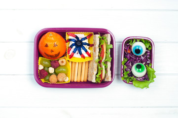 Open Halloween lunch box with school lunch on white wooden background