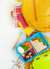 Open lunch box with sandwich, vegetables, fresh berries near school accessories