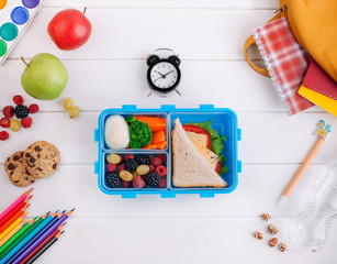 Foto op Canvas Assortiment Lunch box on the white wooden background near clock, school accessories