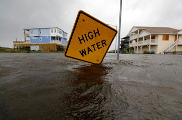 Flood waters lap at a high water warning sign that was partially pushed over by Hurricane Florence on Oak Island, North Carolina