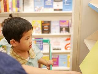 Little Asian baby being happy picking a book at a book store together with her mother - engaging a baby in reading by allowing them to choose a book for herself