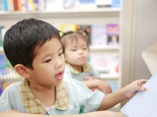 Little Asian baby being happy picking a book at a book store together with her mother - engaging a baby in reading by allowing the baby to choose a book for himself / herself