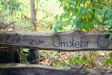 Zeit zur Umkehr, Schrift auf Holzbalken