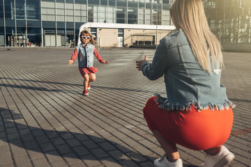 Beautiful Young Mother with Small Stylish Daughter Walks Through City Together