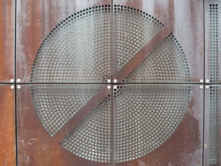 industrial rusty metal plates with round perforated circular grid pattern