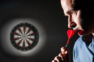 Aim for your goal: player with a red dart focusing his target