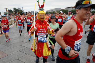 A participant dressed as Monkey King runs past Tiananmen Square during the annual Beijing Marathon in Beijing