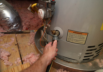 Hand attaches hose to drain water heater
