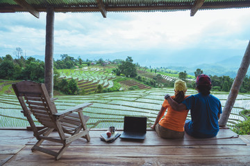 Lover woman and man Asian travel nature. Travel relax. The balcony of the resort. View of the field on the Moutain in summer. Thailand
