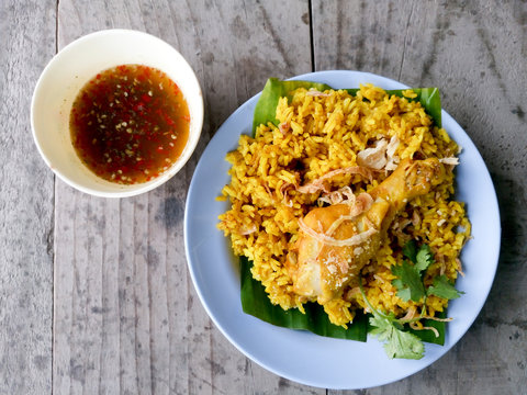 Muslim yellow rice with chicken and sauce on wooden.