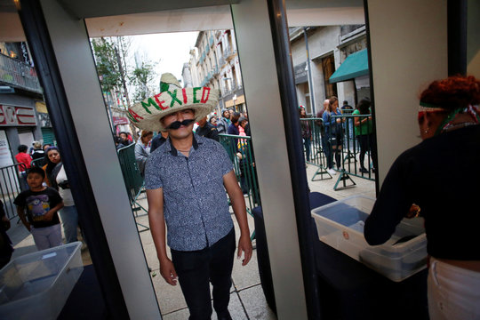 A man wearing a Mexican hat passes by a metal detector while arriving at Zocalo square for the celebration of the anniversary of Mexico's independence from Spain, in Mexico City