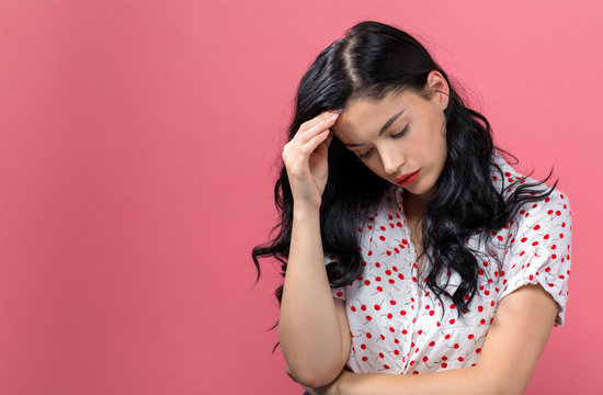Young woman suffering from headache on a solid background