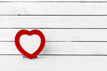 Red Heart Frame over white wood background