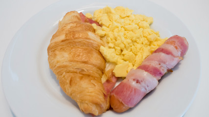 Croissant cheese Sausage, bacon,.scrambled eggs on white dish close up