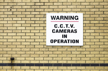 CCTV camera in operation sign on brick wall