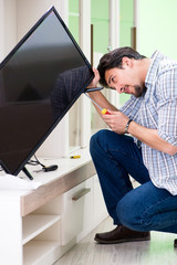 Young man husband repairing tv at home