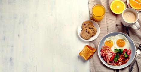 Breakfast with fried eggs, bacon, orange juice, yogurt and toasts