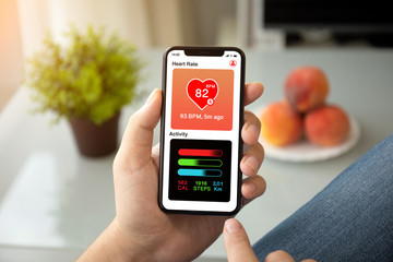 man hands holding phone with app heart and activity screen