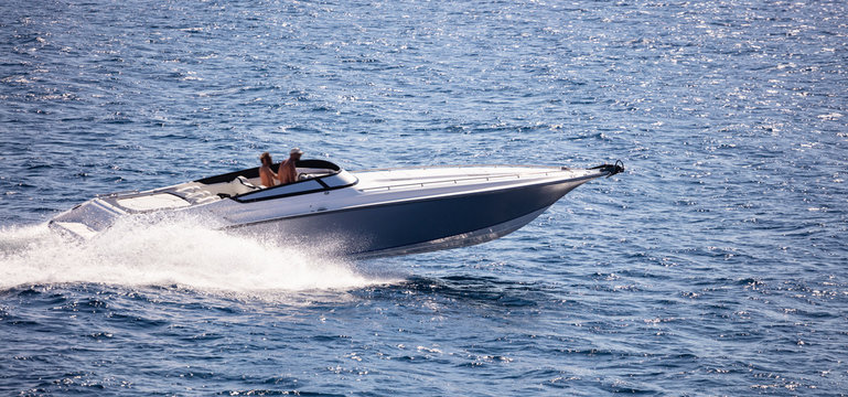 High-speed boat goes fast in calm sea. People enjoy the summer sport.