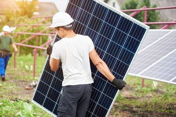 Back view of young worker in protective helmet carrying big shiny solar photo voltaic panel to almost finished exterior metal platform on sunny summer warm day. Renewable ecological green energy.
