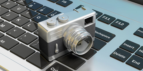 Retro camera, on computer keyboard, 3d illustration.