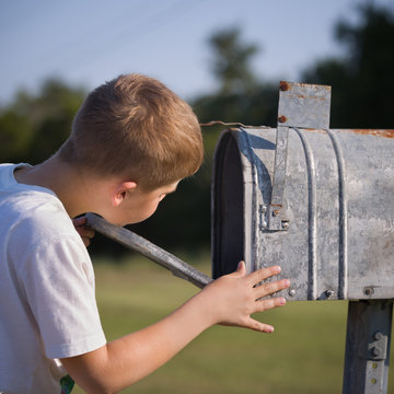 Closeup of cute boy opening a post box and checking mail. Kid waiting for a letter, checking correspondence and looking into the metal mailbox.