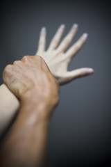 Man holding female hand in the act of violence