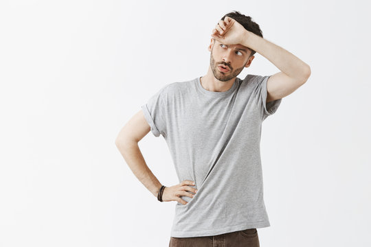 Phew so close. Portrait of relieved handsome dark-haired man with beard in grey t-shirt whiping sweat from forehead breathing out with folded lips and gazing left, solving hard problem