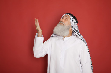 Senior Arab with a checkered veil pointing up and looking away isolated on red background