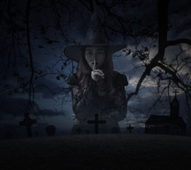 Halloween witch showing silence sign with finger over lips standing over grass, dead tree, cross, birds with church over spooky cloudy sky, Halloween mystery concept