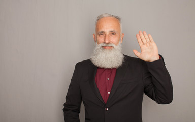 Hello! A happy middle aged bearded man shows his hand a greeting sign.