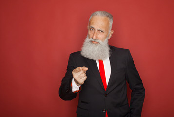 Portrait of a confident senior businessman pointing finger at camera isolated over red background