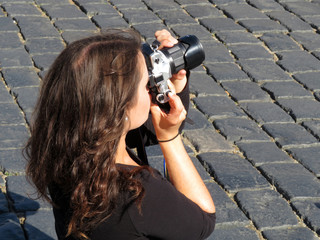 Young woman with a SLR camera in her hands. Girl photographing outdoors