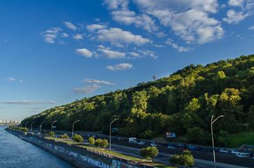Bright white clouds under green city hills