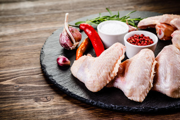 Raw chicken wings on black stone on wooden background