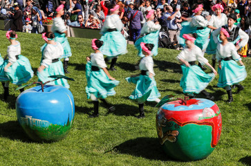Dancers perform next to painted apple-shaped figures during the Apple Festival at City Day celebrations in Almaty