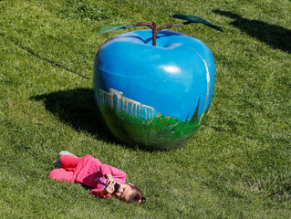 A girl with a mobile phone lies on a lawn next to a painted apple-shaped figure during the Apple Festival at City Day celebrations in Almaty