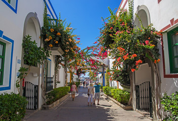 Beautiful narrow street in Canary Islands, Spain, walls covered with bougainvillea colorful flowers