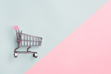 Close up of supermarket grocery push cart for shopping with black wheels on white background. Concept of shopping.