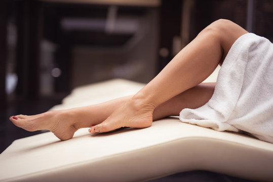 My lower body. Close up of female legs with perfect skin. Woman relaxing on daybed at spa lounge